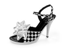 Gift for a lady (with clipping paths). Leather high heel shoe with a white gift bow isolated on white background. Image includes two clipping paths, one of the stock images