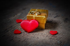 Gift and a lot of hearts on a wooden surface Royalty Free Stock Photography