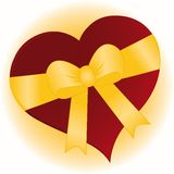 Gift of Love. Large red heart gift wrapped with a gold bow ready to give away Royalty Free Stock Photo