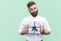 Gift with love. Interesting bearded young adult man with a gift box on light green background. Stock Photography