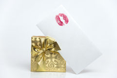 Gift with love. Present in a golden box and envelope with red lipstick mark Royalty Free Stock Photos