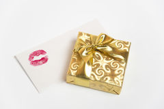 Gift with love. Present in a golden box and envelope with red lipstick mark Stock Photo