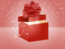 Gift. A gift with a magical glow with bow in red Royalty Free Stock Image