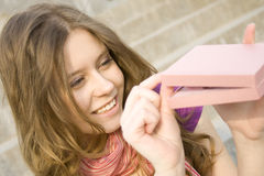 Gift for me. Young woman sitting on the stairs to the street, and holds a pink gift box Stock Photos