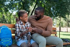 Nice positive man giving a small present to his son. Gift from me. Nice positive men smiling while giving a small present to his son stock photos