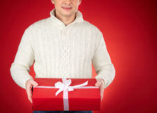 Gift from me. Young man in white knitted sweater showing red giftbox Royalty Free Stock Photo
