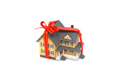 Gift miniature house with red ribbon isolated Stock Photos