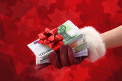 Gift of money. Womans hand with red glove holding gift of money Royalty Free Stock Photos