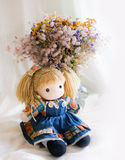 Gift for my girl. Photo with doll and bouquet on a light background Stock Image