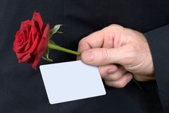 Gift for my love. Man hand with card and red rose royalty free stock photo