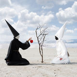 The gift. Mysterious person dressed in black giving an apple from the dry tree to another person dressed in white Stock Photo