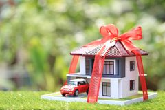 Gift new home and Real estate concept,Model house with Red ribbon and the car on natural green background royalty free stock images