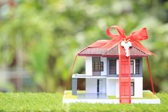 Gift new home and Real estate concept,Model house with Red ribbon on natural green background stock image