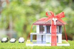 Gift new home and Real estate concept,Model house with Red ribbon on natural green background royalty free stock photos