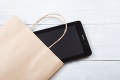 Gift - new tablet pc on wooden background Stock Image