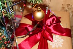 A gift for the New Year or Christmas or any other holiday. A gift for the New Year or Christmas with a decoration on the background of a Christmas tree Royalty Free Stock Photos