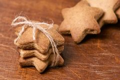 Gift for new year. Gingerbread stars. Delicious dessert. Dark brown background Stock Photography