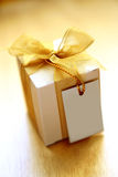 Gift with a note. A small box of appreciation gift. Golden yellow tinted to enhance the mood. Shallow depth of field shot is intentional. Note is left empty for Stock Photo
