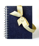Gift notebook. The gift notebook decorated with a gold ribbon bow Stock Images