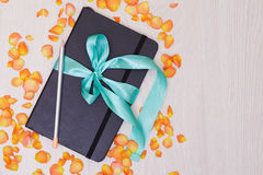 Gift notepad with ribbon on the table. Pencil and sketchbook. Stock Image
