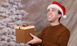 Gift Offer. A young man wearing a Santa hat is holding and offering a gift to someone the viewer can't see Stock Image