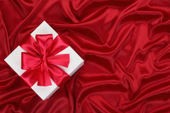 Gift On The Red Silk. Royalty Free Stock Photography