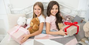 A gift opening cheer. Cute little girls with presents in bed. Opening presents on Christmas morning. New Year surprise stock images