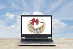 Gift and with origami lucky stars on laptop screen Royalty Free Stock Photography
