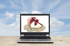 Gift and with origami lucky stars on laptop screen Royalty Free Stock Photo