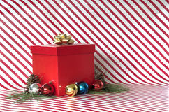 Gift and ornaments on candy cane stripes Royalty Free Stock Images