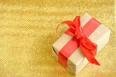 Gift. A gift in a package with a big red bow on a gold background royalty free stock photography