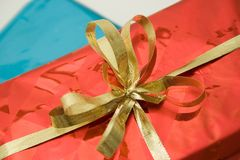 Gift Package Bow. Gold Ribbon Bow on Shiny Red Gift Box Royalty Free Stock Photo