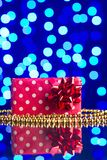 Gift in package and golden beads on a glass table with a beautiful blue bokeh Royalty Free Stock Images