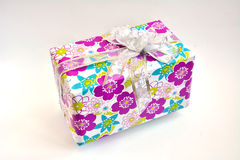 Gift. A gift in a package with a nice bow and purple flowers stock images
