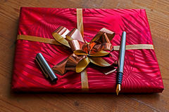 Gift package with open pen on it Stock Photo