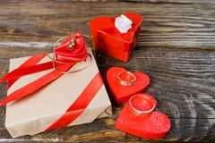The gift is Packed in Kraft paper and tied with a red ribbon with a rose in the center of which lies a pendant in the shape of clo royalty free stock photos