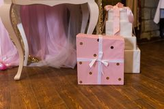 The gift is packed in pink paper with golden circles and bandaged with a white ribbon. Stock Photos