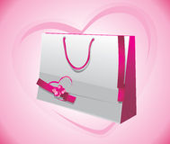 Gift paper bag with ribbons on the pink background Stock Photos