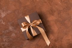 A gift in a paper box is decorated with a satin ribbon and a bow on a brown background. Festive concept.Flat layout. stock image
