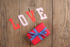Gift and paper letters forming word LOVE Stock Photos