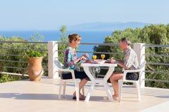 Gift par som äter på tabellen på terrass nära havet arkivfoto