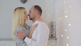 Gift par som hemma kysser nära felika ljus stock video