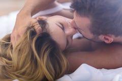 Gift par som kysser i säng Royaltyfri Foto