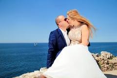 Gift par som kysser och sitter vid havet arkivbilder