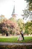 Gift par som kysser på ett fält för grönt gräs med träd och gammal domkyrka i bakgrund royaltyfria bilder