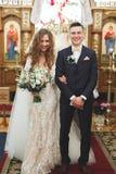 Gift par som poserar i en kyrka efter ceremoni Royaltyfri Fotografi