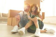 Gift par som sitter nära kartonger i en ny lägenhet arkivfoton