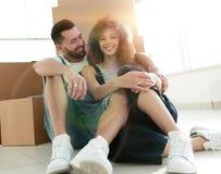 Gift par som sitter nära kartonger i en ny lägenhet royaltyfri foto