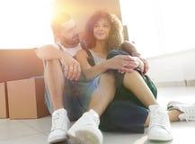 Gift par som sitter nära kartonger i en ny lägenhet arkivbild