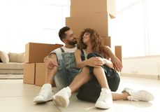 Gift par som sitter nära kartonger i en ny lägenhet royaltyfria bilder